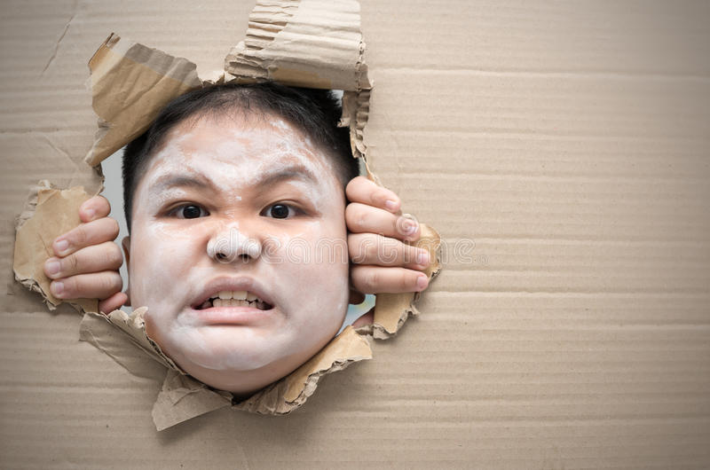 Ghost kid angry and looking through hole on cardboard. stock photo