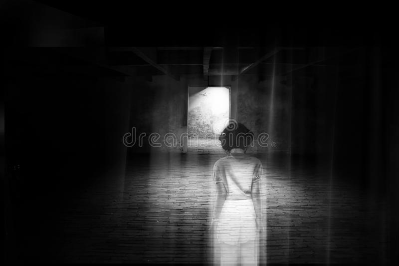 Ghost little girl appears in old dark room, ghost in haunted house, child is confined to death. royalty free stock photo