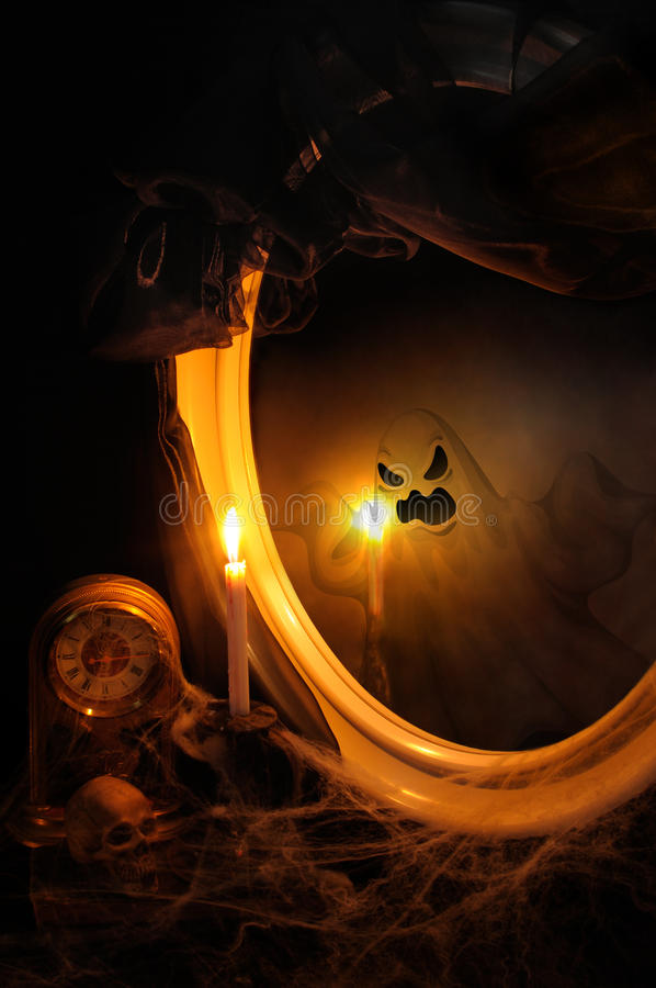 The ghost in the mirror. Ghost reflection in the mirror on the table with a candle, clock, shrouded in cobwebs stock photo