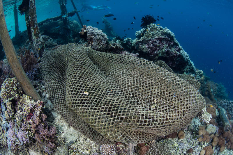 Ghost Net on Coral Reef in Raja Ampat. A discarded fishing net has drifted onto a coral reef in Raja Ampat, Indonesia. This remote region is the heart of the stock photos