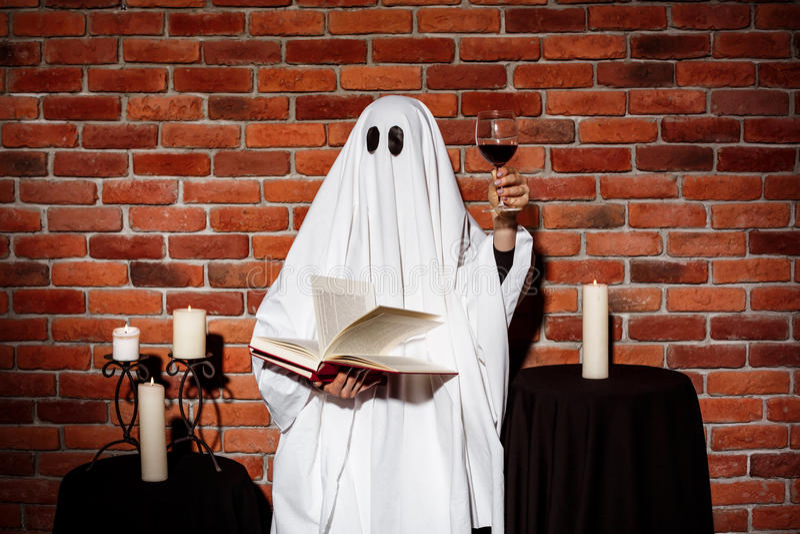 Ghost que guarda o livro e o vinho sobre o fundo do tijolo Partido de Halloween foto de stock royalty free