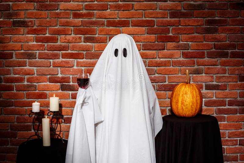 Ghost que guarda o vinho sobre o fundo do tijolo Partido de Halloween imagens de stock