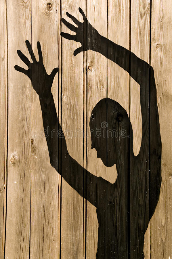 Ghost Shadow on a wooden wall. A ghost shadow or silhouette of a woman against a wooden fence with working path stock photos