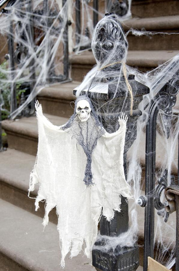 Ghost. A ghost in spider webs hangs from the stair railing for Halloween stock photo