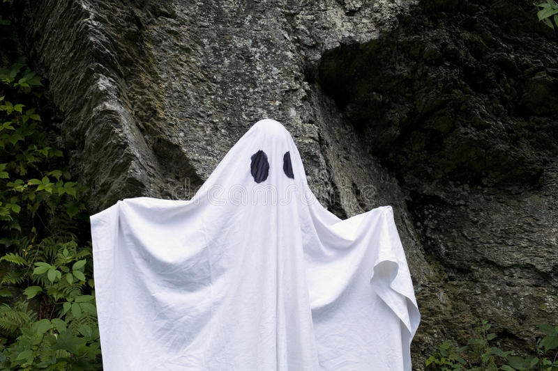 Ghost standing in front of a rock. A spooky white ghost covered by a sheet with slits over the eyes standing in front of a rock royalty free stock images