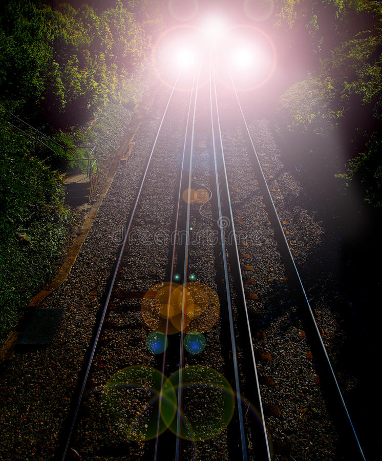 Ghost train. Photo of a speeding train with very bright lamps reflecting on railway tracks up ahead