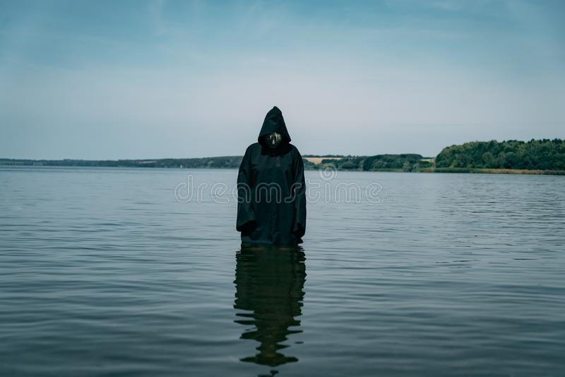 Ghost is in the water in a black cloak in the afternoon. The phantom looks creepy.  stock photography