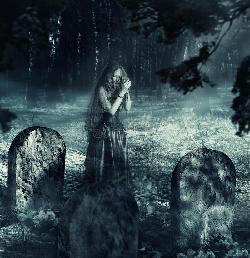 Ghost of woman on night cemetery royalty free stock photo