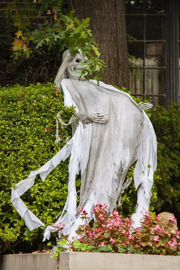 Ghost-zombi enceinte en dehors de décoration de Halloween devant une maison et une haie avec des fleurs en bas photo libre de droits