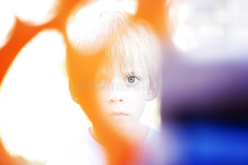 Ghostly boy. Small blond boy peeking behind playground equipment showing one eye