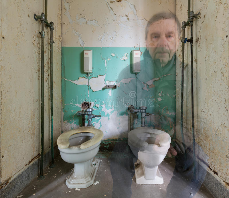 Ghostly man on toilet in Trans-Allegheny Lunatic Asylum. Ghostly senior man sitting on toilet inside Trans-Allegheny Lunatic Asylum in Weston, West Virginia, USA royalty free stock image
