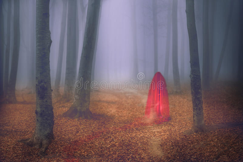 Ghostly red figure in foggy beautiful forest royalty free stock photo