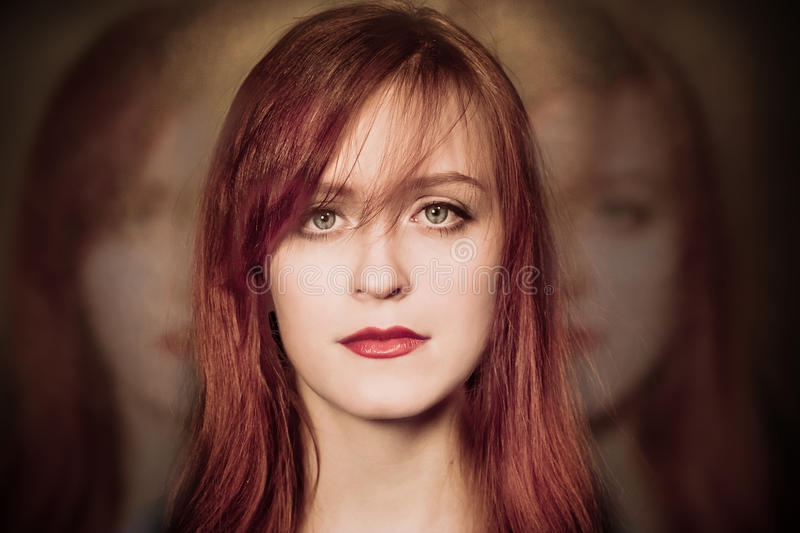 Ghosts behind her. Redhaired woman and a ghost behind her royalty free stock photography