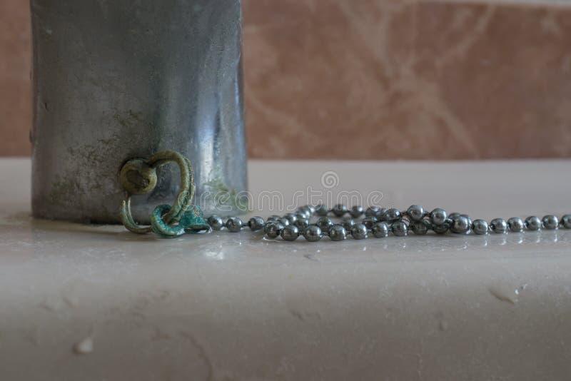 Giacimenti del calcio sul tappo a catena del lavandino del bagno immagini stock libere da diritti