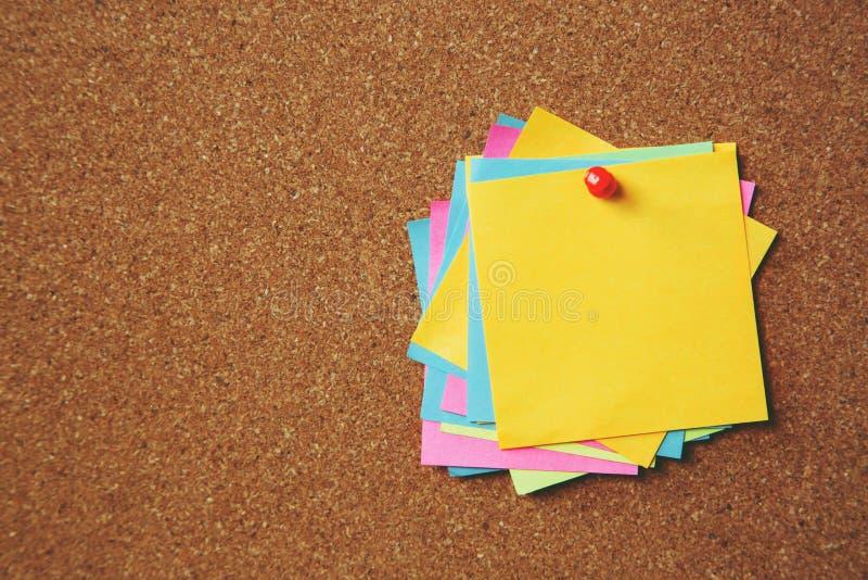 Giallo appiccicoso della carta del perno delle note di ricordo di carta del blocco note sull'albo del sughero fotografia stock