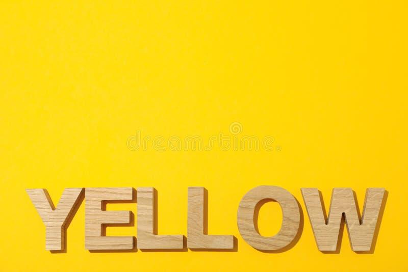 Giallo di parola presentato nelle lettere di legno fotografia stock