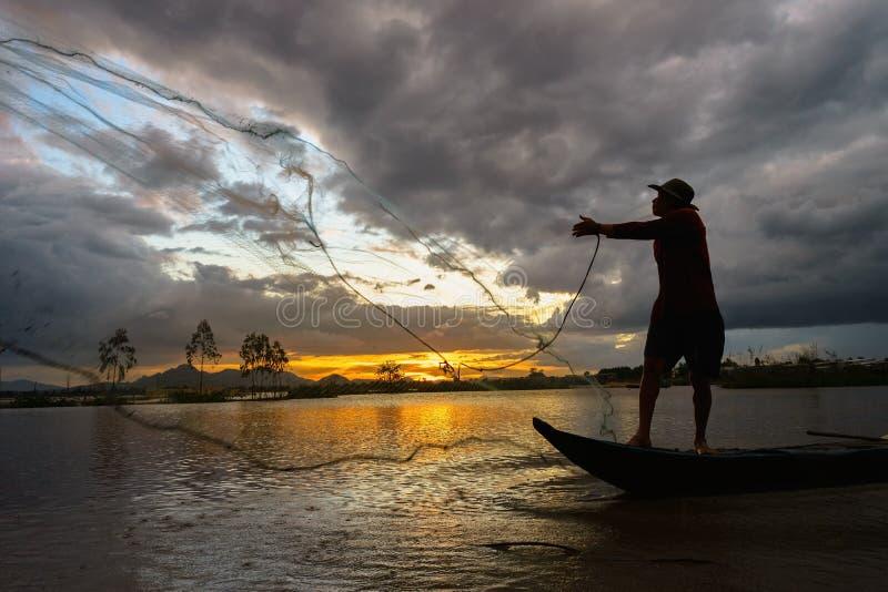 An Giang, Vietnam - 6 de diciembre de 2016: Puesta del sol en campo cultivado con los pescadores que cogen pescados lanzando la j foto de archivo libre de regalías