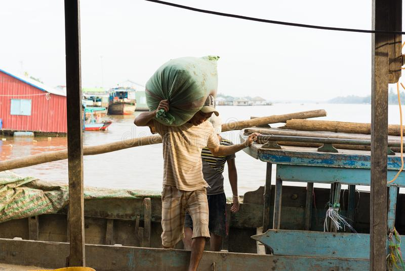 An Giang, Vietnam - Nov 29, 2014: Worker carries heavy bag of fish food from small wooden transportation boat to floating fish far royalty free stock photos