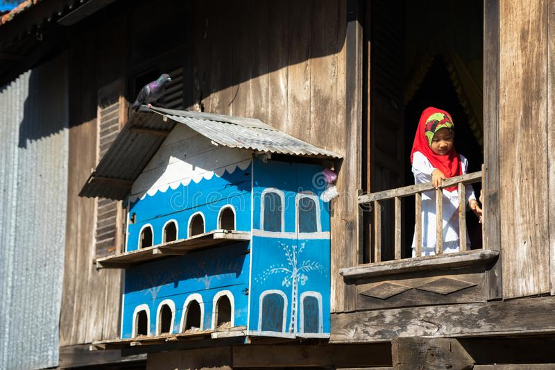 An Giang, Vietnam - Sep 6, 2016: Champa house windows with Vietnamese muslim girl and pigeon house in a champa village, Khanh Hoan. District, South Vietnam royalty free stock photos