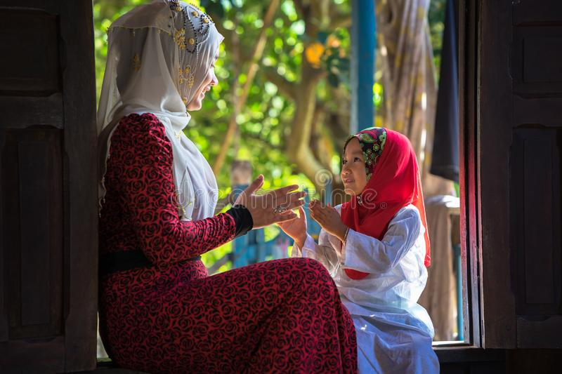An Giang, Vietnam - Sep 6, 2016: Vietnamese muslim girl wearing traditional red dress playing with her sister in a champa village, stock photos