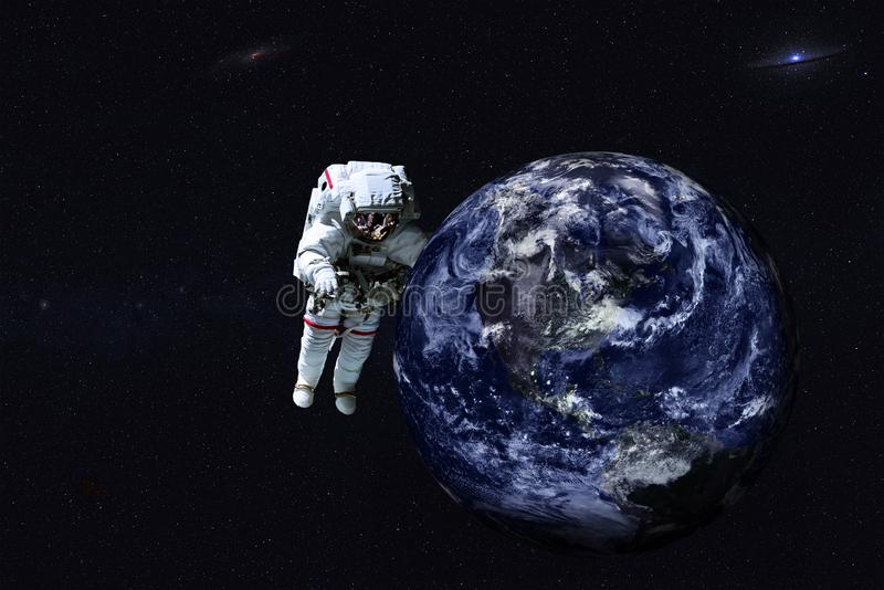 Giant astronaut near Earth planet of Solar system. royalty free stock photo