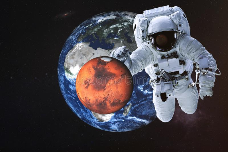 Giant astronaut near Mars and Earth planets stock photo