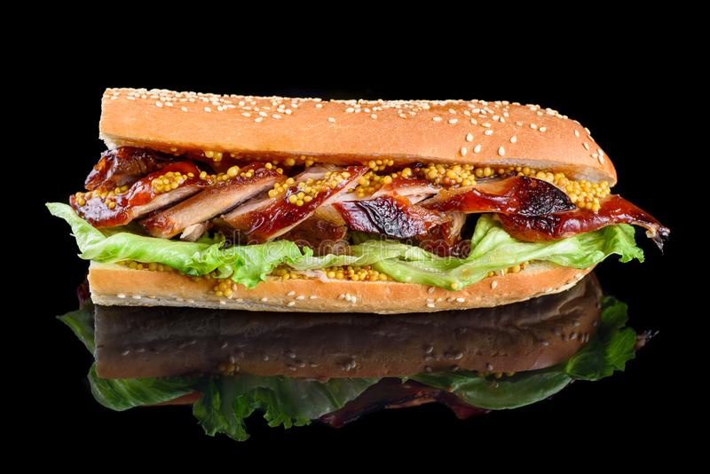 Giant BBQ Rib Sandwich with salad leaf and French mustard in baguette. isolated on a black background stock photos