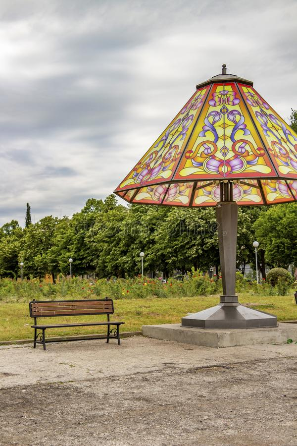 Free Giant Bedside Lamp And A Bench In A Public Park Under An Overcast Summer Sky Royalty Free Stock Image - 136006926