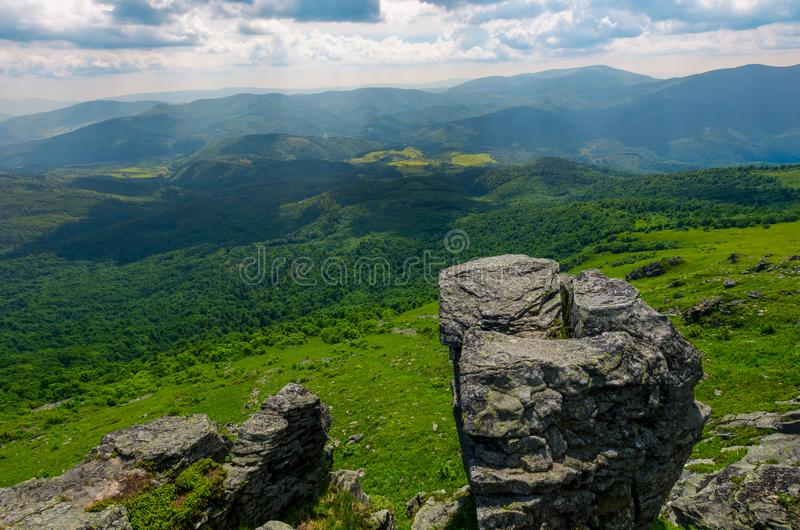 Giant boulder on a cliff over the grassy hillside stock photos