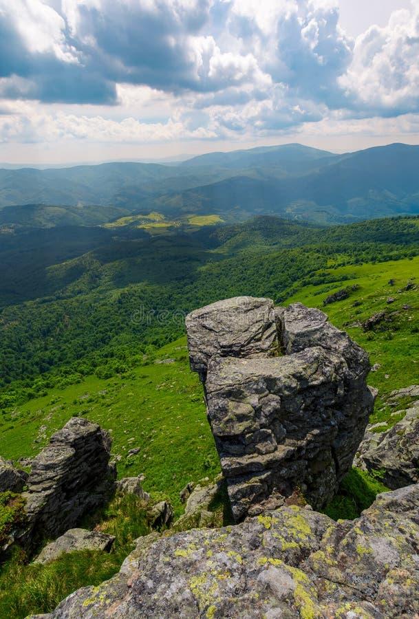 Giant boulder on a cliff over the grassy hillside stock image
