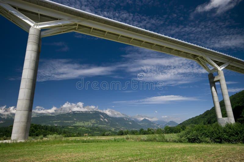 Giant bridge and the alps stock photography