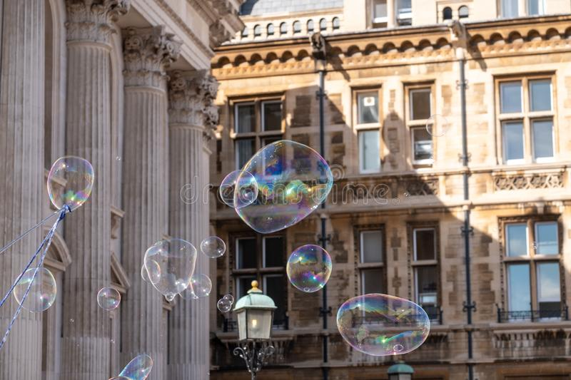 Giant bubbles blown for tourists outside Senate House and Gonville and Caius College in Cambridge town centre, UK. Giant bubbles blown for tourists outside stock images