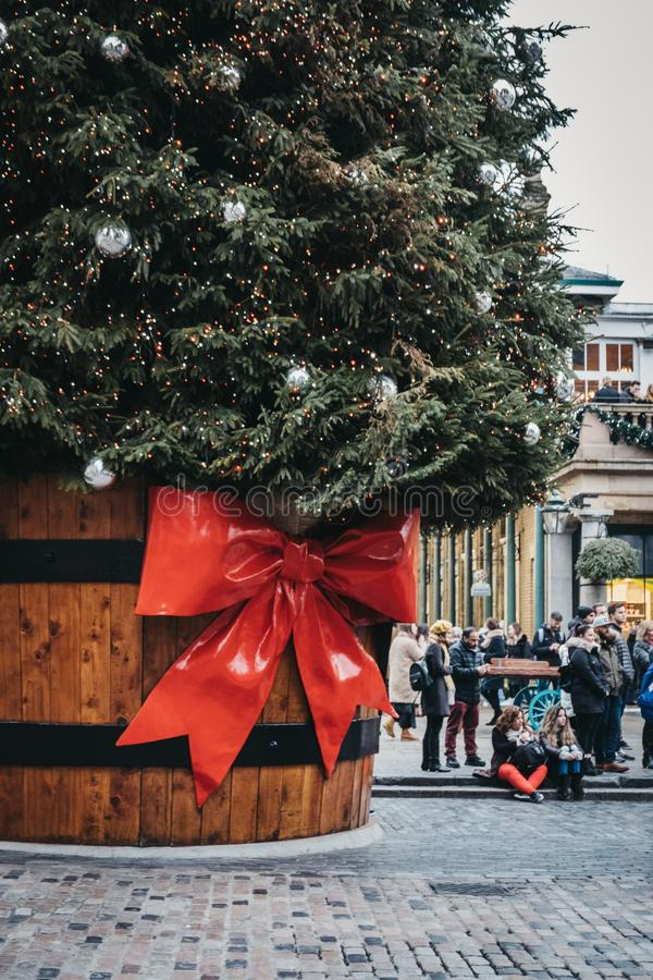 Giant Christmas tree in a pot with a gift tag in front of Covent Garden Market, London, UK. London, UK - January 5, 2019: People walking by the Giant Christmas royalty free stock photography
