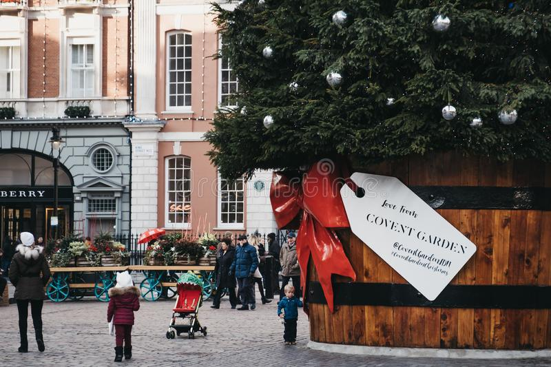 Giant Christmas tree with a gift tag in Covent Garden Market, London, UK. Giant Christmas tree in a pot with a gift tag in front of Covent Garden Market, one of royalty free stock image