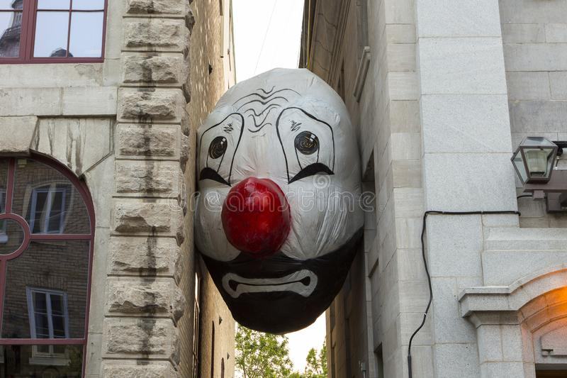 Giant clown head balloon from the Endgame Nadd & Nell Max Streicher installation between two buildings. During the 2019 Passages insolites art show in Quebec royalty free stock photo