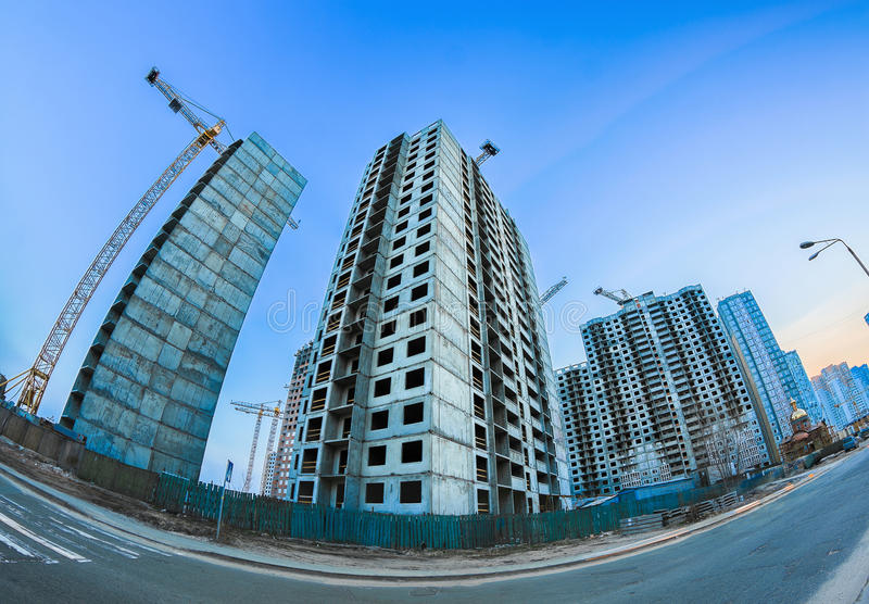 Giant concrete buildings. The construction of modern concrete prefabricated houses and christian church royalty free stock images
