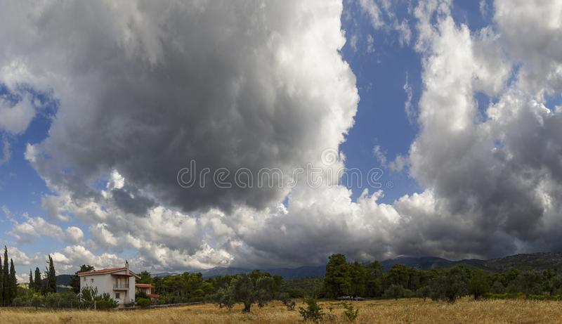 Giant Cumulus clouds before the approaching may storm in a village on the Greek island of Evia. Giant Cumulus clouds before the approaching may storm in a royalty free stock photo