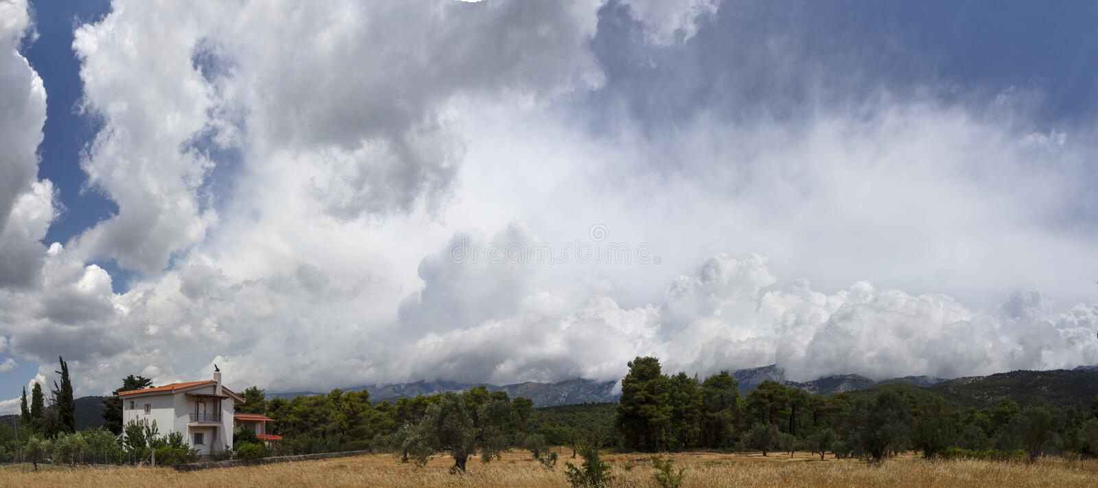 Giant Cumulus clouds before the approaching summer storm in a village on the Greek island of Evia stock image