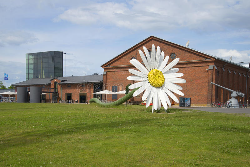 Giant daisy flower on background of the building of the exhibition center Forum Marinum. Turku, Finland. TURKU, FINLAND - JUNE 13, 2015: Giant daisy flower on royalty free stock photo