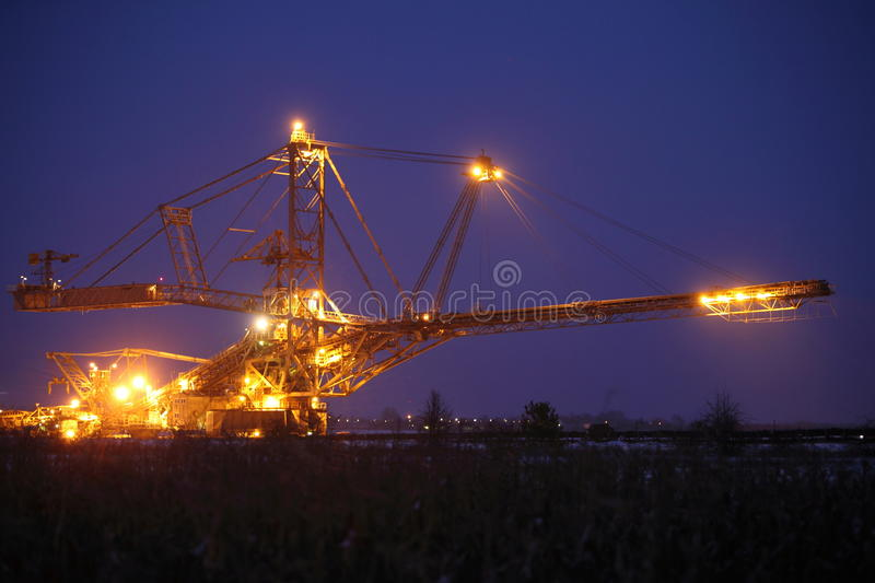 Giant excavator in a coal open pit evening. Bucket wheel excavator digging for brown coal night view Poland extractive industry royalty free stock photos