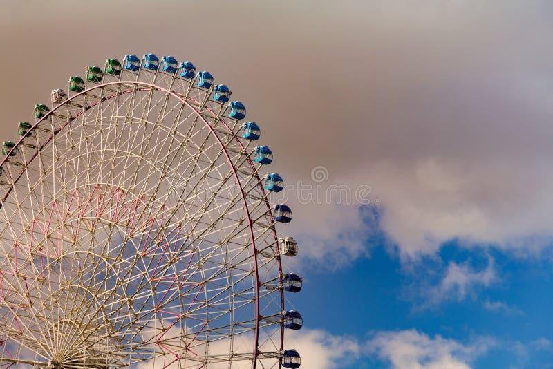 Giant ferris flyer wheel against blue sky. In amusement park stock photo