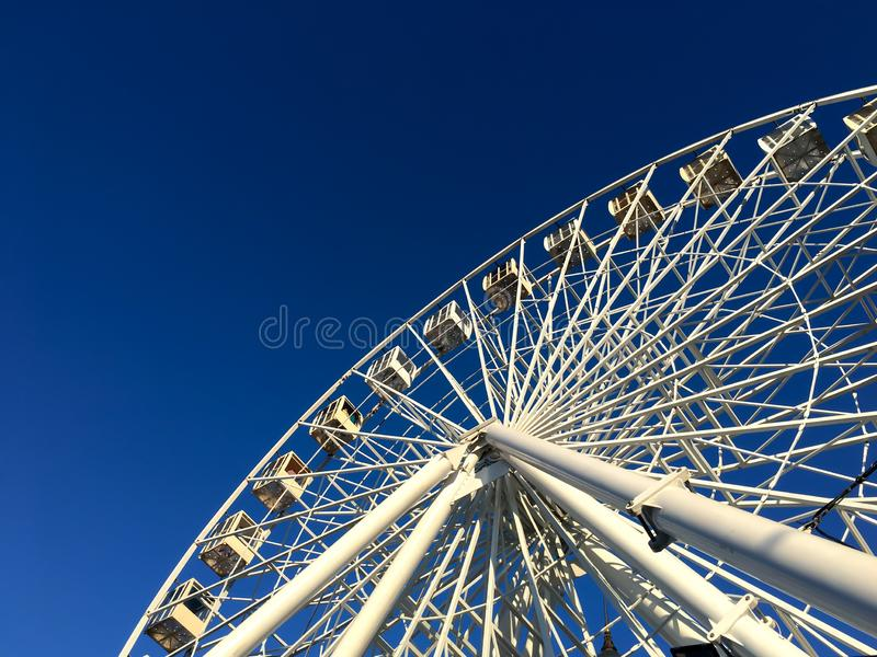 Giant ferris wheel against a blue sky in a minimalist style, simple geometric shapes royalty free stock images