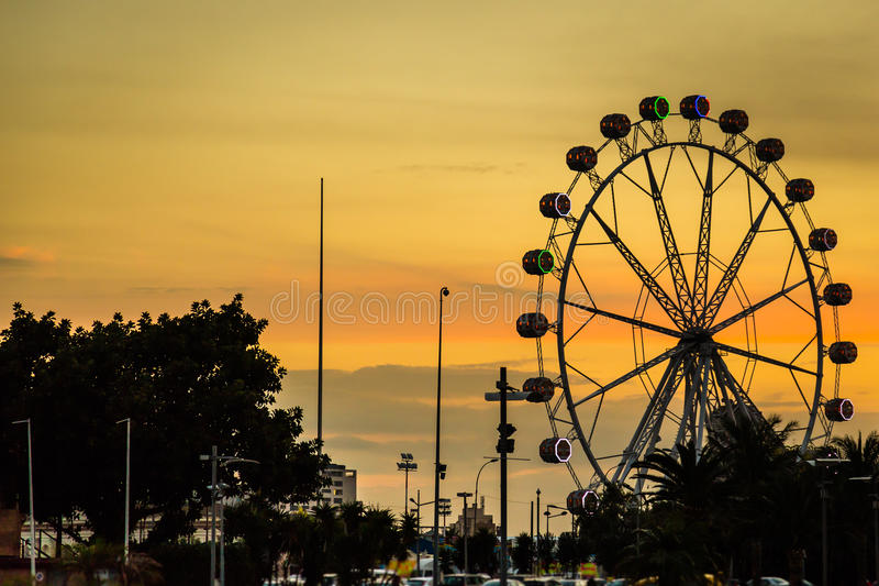 Giant ferris wheel Valencia Spain. Giant white ferris wheel during sunset behind the Port Authority building in Valencia Spain royalty free stock photography