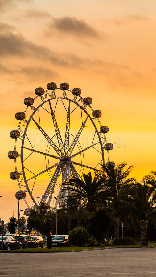 Giant ferris wheel Valencia Spain. Giant white ferris wheel during sunset behind the Port Authority building in Valencia Spain royalty free stock images