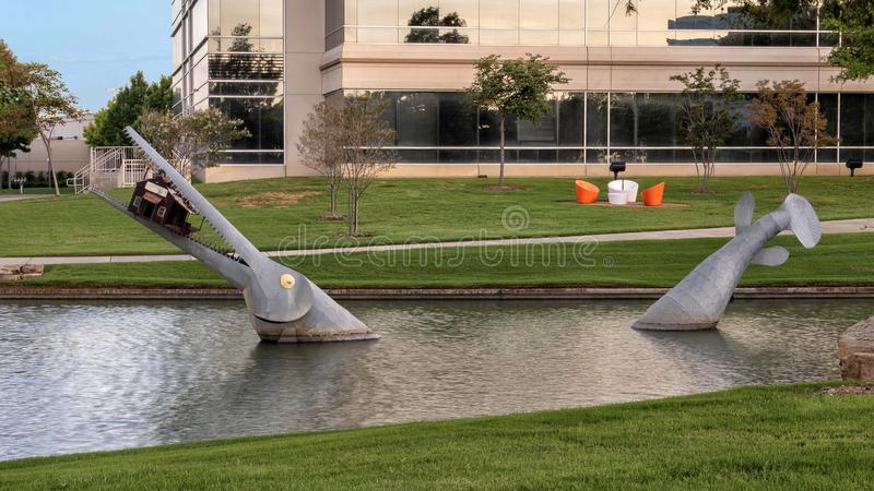Giant fish eating a house by Joe Barrington, Hall Park, Frisco, Texas. Pictured is a steel sculpture by Joe Barrington of a giant fish eating a house in a pond royalty free stock photos