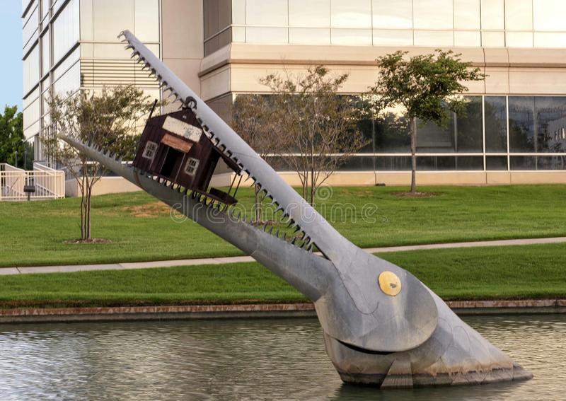 Giant fish eating a house by Joe Barrington, Hall Park, Frisco, Texas. Pictured is a steel sculpture by Joe Barrington of a giant fish eating a house in a pond stock images
