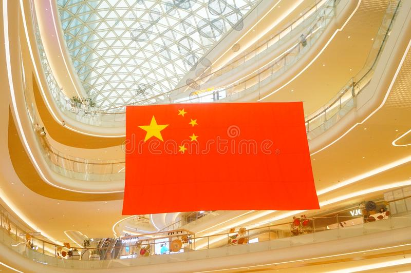 Shenzhen, China: a giant five-star red flag hangs in a shopping mall to greet National Day royalty free stock photo