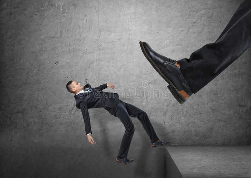 Giant foot in black shoe kicking little businessmen off the edge, and he is falling down royalty free stock photo