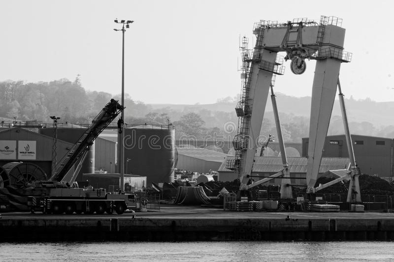 Giant A Frame and crane on dockside. At Montrose Harbour in Scotland. Industrial buildings with hills beyond royalty free stock images