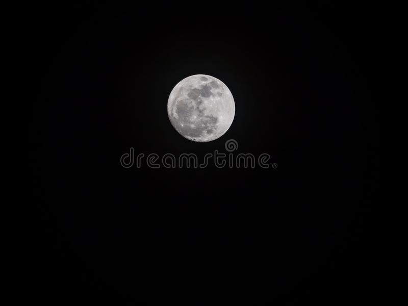 A giant full moon from supermoon phenomenon where the moon is or. Bited near to the earth. The moon is in an isolated black background stock photo